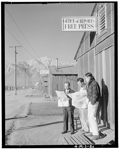 Ansel Adam's photo 'Roy Takeno (Editor) and group reading Manzanar paper [i.e. Los Angeles Times] in front of office, Yuichi Hirata, Nabuo Samamura, Manzanar Relocation Center, California'